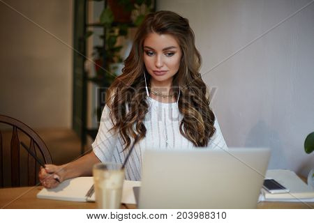 Indoor shot of confident serious young European woman blogger with voluminous hair concentrated on work sitting at cafe table in earphones using laptop computer and writing down in copybook