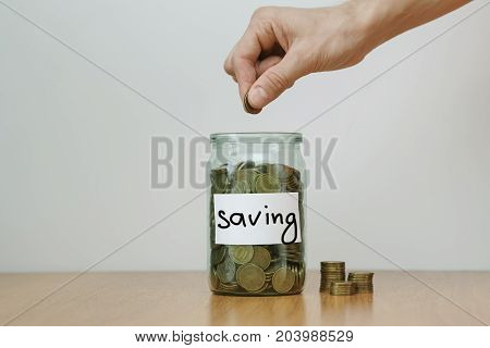 Distribution Of Cash Savings Concept. Hand Puts Coins To The Glass Money Boxes With Inscription 'sav