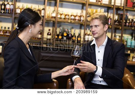 Woman Send Wine To Man With Attracitve Smiling At Restaurant. People Drinking Wine With Relax Emotio