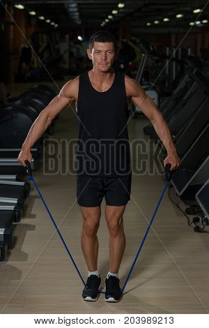 Fitness Man Exercising With Stretching Band In The Gym. Muscular Sports Man Exercising With Elastic