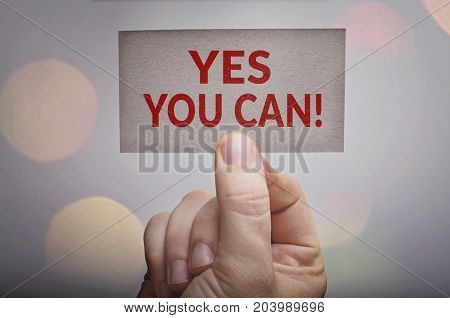 Yes you can! motivational card in hand with bokeh lights background