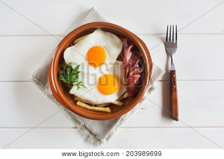 Traditional spanish lunch - fried eggs with french fries, cured pork slices of jamon and parsley on the white wooden table