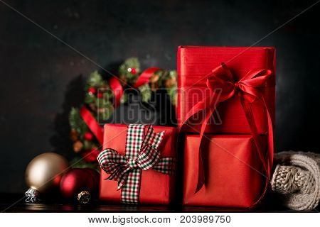 Giftboxes wrapped in red paper arranged with ornamental balls and wreath on background.
