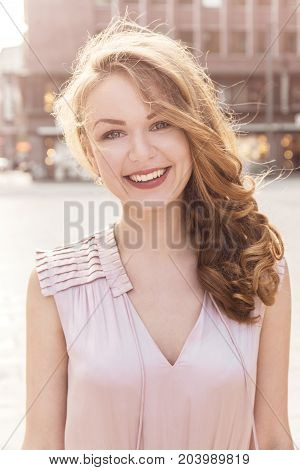 Portrait of cheerful woman in stylish clothing and with hairstyle smiling at camera on background of street.