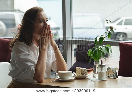 Beautiful Sad Female Sitting Alone At The Cafe. Sad Young Woman Deep In Cafe. She Is Sad