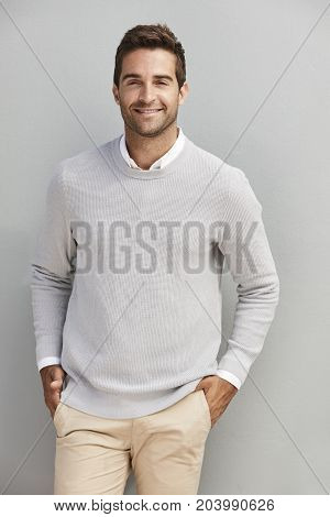 Smiling handsome dude in grey sweater portrait