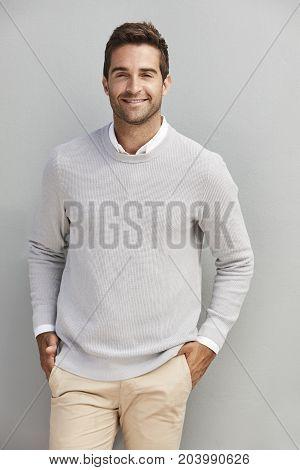 Smiling handsome dude in grey sweater portrait