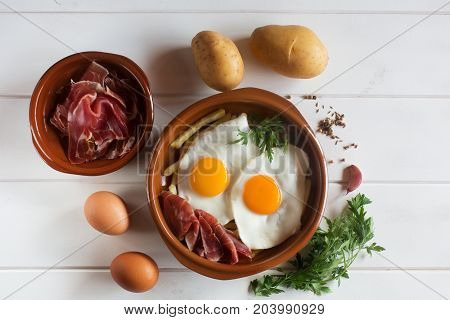 Traditional spanish lunch - fried eggs with french fries, cured pork slices of jamon on the white wooden table. Dish is surrounded by ingredients