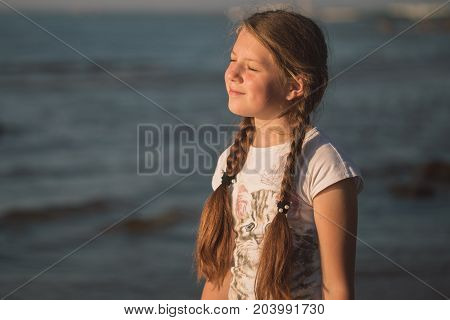 young girl enjoys the warmth of the sun