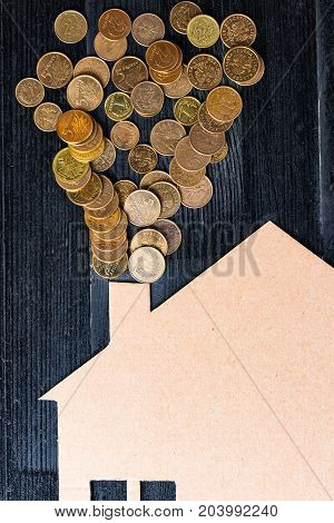 Home heat savings or expenses concept. Coins coming out of a chimney of house shape.