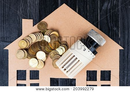 Home heat savings or expenses concept. Home heat savings or expenses concept. Coin stacks radiator regulator house shape.