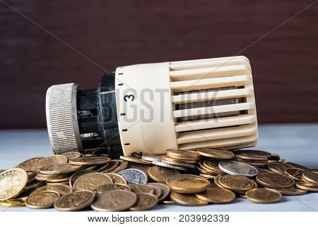 Home heat savings or expenses concept. Radiator regulator on a heap of coins. Copy space at the top.