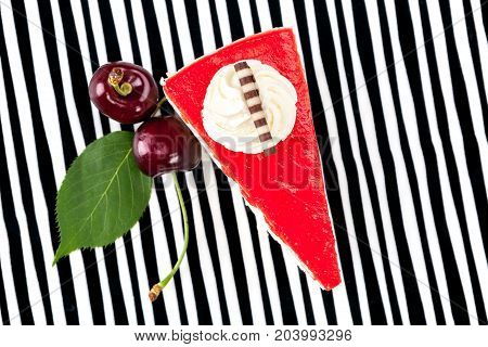 Delicious cherry cake with cherries on striped background from above.