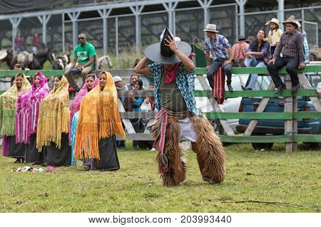 May 27 2017 Sangolqui Ecuador: indigenous dancer wearing furry chaps and large hat performing at the opening of a rural rodeo