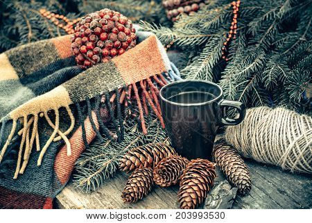 Cup of hot tea on a rustic wooden table. Still life of cones twine packthread fir branches. Preparing for Christmas.