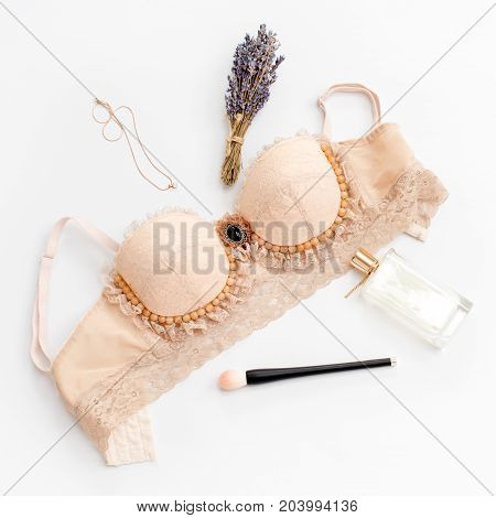 Glamorous stylish sexy lace lingerie with woman accessories on white background. Woman lace bra with dried lavender and necklace, flat lay, top view. Fashion concept, textile, jewelry, underwear