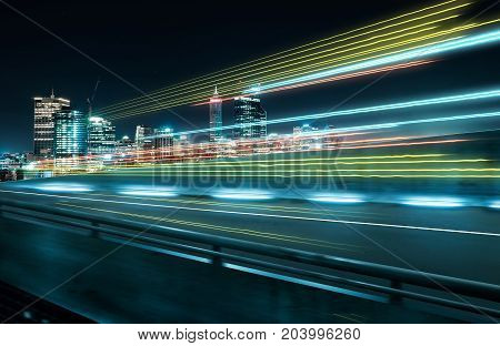 View from Side of flyoverblurred motion effect with light trails and beautiful city skyline background .