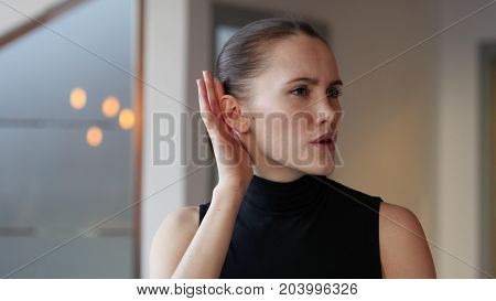 Woman Listening Secret Carefully at Work in Office
