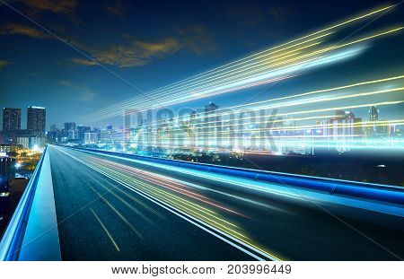 Empty asphalt flyover with city skyline and light trails night scene .