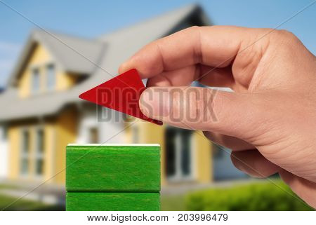 Hand with building bricks and house in the background