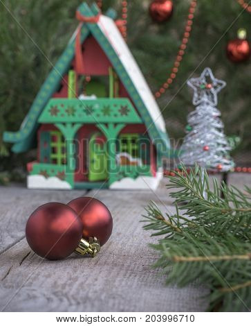Toy house with Christmas decoration in front. Christmas background and decorations. Soft focus.