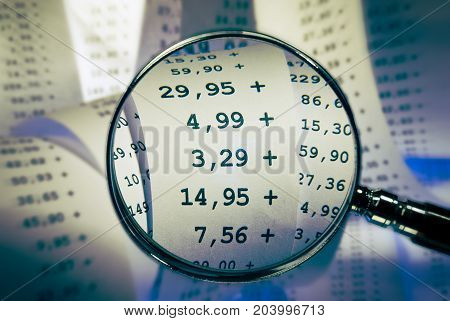 Magnifier focused sums on a receipt with other tokens in the background