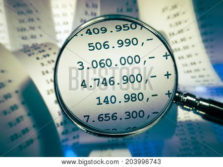 Magnifier focussing high sums in front of a background with receipts