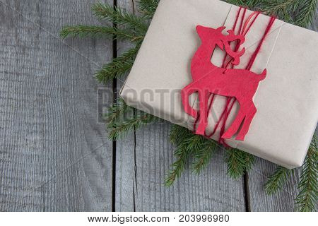 Christmas gift box on rustic table decor reindeer handicraft wrapping parchment fir tree twigs. Top view with copyspace.