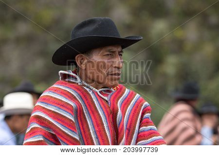 May 27 2017 Sangolqui Ecuador: closeup of a quechua cowboy wearing a traditional wool poncho at a rural rodeo event in the Andes