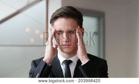 Headache Tense Young Businessman in Office at Work