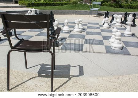One brown chair near the street chessboard with chessmen