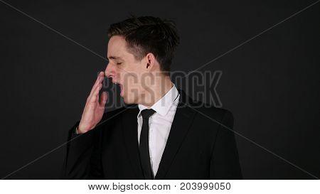 Yawning Tired Businessman Dark Black Background in Studio