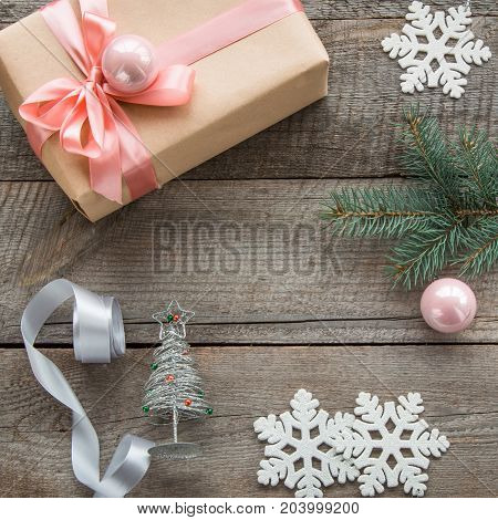 Preparation for Christmas holiday. Christmas gift box with pink ribbon and ball decor from snowflakes silver ribbon and decor around. Top view and inside copyspace. Flat lay.