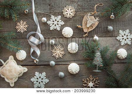 Christmas decor laid out on a wooden surface. Fir branches silver ribbon and ball white marshmallow snowflakes toy deer and decor around. Top view and copyspace. Flat lay. Shabby-chic