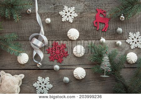 Christmas decor laid out on a wooden surface. Fir branches silver ribbon and ball white marshmallow snowflakes toy red deer and decor around. Top view and copyspace. Flat lay.