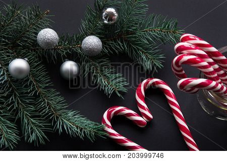 Christmas candy cane with silver evening balls and green fir tree on black background. Christmas concept. Top view and copy space close up.