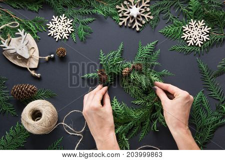 Preparation for Christmas holiday. Christmas workshop of wreath decor twine twigs and snowflakes. Woman prepare a wreath. Top view and copy space. Flat lay. Workshop.