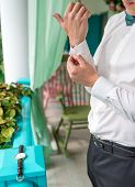 Man buttoning cuff on luxury white shirt sleeves. Close up of man hand wears white shirt and cufflinks. Groom fixes cufflinks standing on veranda outdoors poster