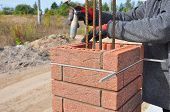 Bricklayer Worker Installing Red Clinker Blocks around Iron Bar and Caulking Brick Masonry Joints Exterior Wall with Trowel Putty Knife and Fixing with Spirit Level Outdoor poster