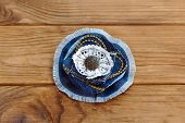 Blue denim floral brooch or hair accessory isolated on a wooden table. How to Recycle old jeans into a new jewelry. Beautiful handmade flower made from recycled materials. Cheap craft idea for adults poster