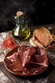 a plate with some slices of serrano ham on a rustic wooden table, next to a cruet with olive oil and a sandwich of typical catalan pa amb tomaquet, bread with tomato, stuffed with serrano ham poster