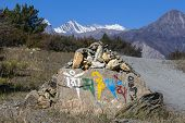 Prayer stones as a form of prayer in Tibetan Buddhism on the hill in Himalaya mountains. Annapurna region Nepal. Buddhist mantra Om Mani Padme Hung on the stone. poster