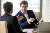 Successful businessman clarifying provisions of contract with business partner, discussing terms of agreement, explaining strategy or financial plan. HR manager asking job candidate about his resume poster
