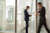 Image of blurry silhouettes of office workers hurrying in business past large window with city view in modern office. Fast and tense rhythm of modern business life, busy businessmen, economical grow poster