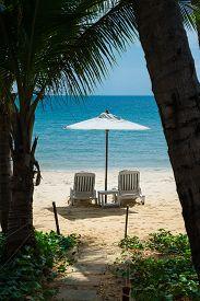 Tropical beach with 2 beach chairs under white umbrella