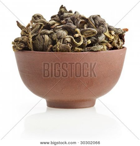 Oriental clay tea cup  with green  tea leaves isolated on white background