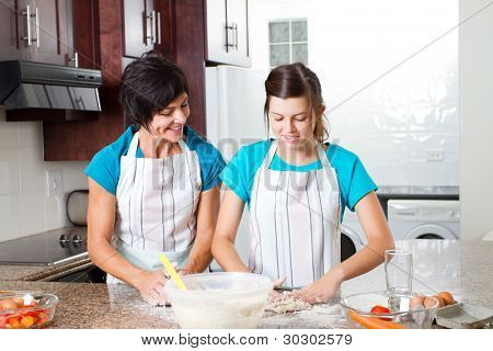 middle aged mother and teen daughter baking in kitchen