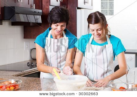 happy mid age mother and teen daughter baking in kitchen