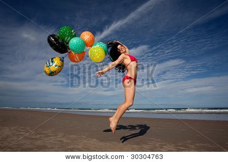 Young Woman At Beach Celebrating Her Birthday With Balloons