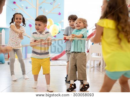 Group Of Kids Play And Pull Rope Together In Day Care. Games And Physical Activity For Children
